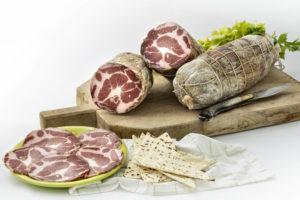 Coppa stagionata di maiale nostrano, prodotta in Gallura, foto su tagliere in legno con spianata
