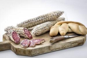 Salame stagionato di puro suino, prodotto in Gallura, foto su tagliere in legno con pattadese