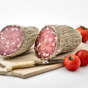 Soppressa stagionata di puro suino, prodotta in Gallura, foto su tagliere con pomodori
